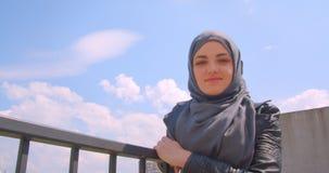 Zbliżenie krótkopęd potomstwo dosyć muzułmański bizneswoman patrzeje na miastowym miasto widoku i obraca kamery ono uśmiecha się  zbiory