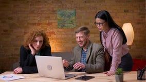 Zbliżenie krótkopęd pracuje na laptopie dostaje szczęśliwy i świętuje sukces z dwa kobietą młody biznesmen zbiory