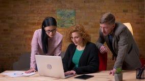 Zbliżenie krótkopęd pracuje na laptopie dostaje szczęśliwy i świętuje sukces z dwa kolegami młody bizneswoman zdjęcie wideo