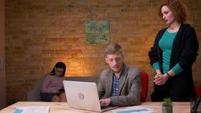 Zbliżenie krótkopęd pracuje na laptopie indoors w biurze młody biznesmen Żeński pracownik mówi on złą wiadomość zbiory wideo