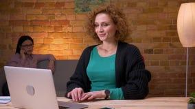 Zbliżenie krótkopęd pracuje na laptopie ma rozmowę telefoniczą relaksuje młody bizneswoman patrzejący kamerę i ono uśmiecha się zbiory
