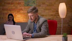 Zbliżenie krótkopęd pracuje na laptopie relaksuje młody biznesmen patrzejący kamerę i ono uśmiecha się indoors w biurze zbiory