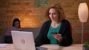 Zbliżenie krótkopęd robi zakupy online na laptopie z kartą kredytową i ono uśmiecha się szczęśliwie indoors w dorosły bizneswoman zbiory wideo