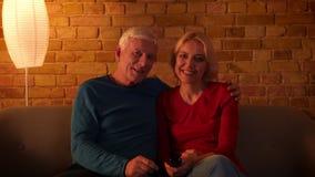 Zbliżenie krótkopęd starsza szczęśliwa para ogląda TV ekranowego uśmiechający się radośnie być relaksującym obsiadaniem na leżanc zdjęcie wideo