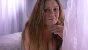 Zbliżenie krótkopęd tłuściuchna seksowna dosyć caucasian kobieta patrzeje kamerę i bawić się z tule w z dużymi piersiami zdjęcie wideo