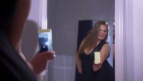 Zbliżenie krótkopęd tłuściuchna seksowna dosyć caucasian kobieta z dużymi piersiami bierze selfies na telefonie przed lustrem zdjęcie wideo