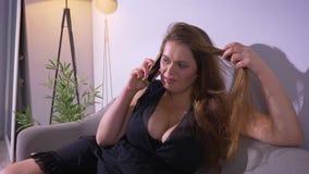 Zbliżenie krótkopęd tłuściuchna seksowna dosyć caucasian kobieta z dużymi piersiami ma rozmowę na telefonie podczas gdy odpoczywa zbiory wideo