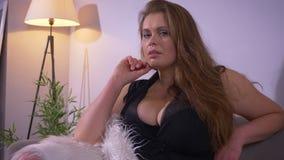 Zbliżenie krótkopęd tłuściuchna seksowna luksusowa caucasian kobieta patrzeje kamerę i pozuje z miękką futerko pokrywą z dużymi p zbiory