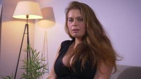 Zbliżenie krótkopęd tłuściuchna seksowna luksusowa caucasian kobieta patrzeje kamerę z dużymi piersiami podczas gdy siedzący na l zbiory wideo