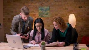 Zbliżenie krótkopęd trzy pracownika dyskutuje dane używać laptopów wykresy i pastylkę indoors w biurze zbiory wideo