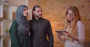 Zbliżenie krótkopęd trzyma pastylki pozycję w niedawno kupującym mieszkaniu młoda szczęśliwa muzułmańska para opowiada realter zdjęcie wideo