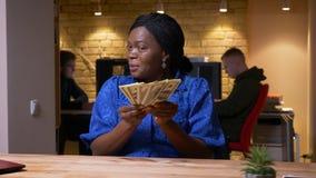 Zbliżenie krótkopęd uśmiecha się kamerę pomyślna dorosła amerykanin afrykańskiego pochodzenia bizneswomanu liczenia gotówka patrz zbiory