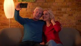 Zbliżenie krótkopęd uśmiecha się radośnie siedzieć na leżance indoors w a starsza szczęśliwa para bierze selfies na telefonie zbiory
