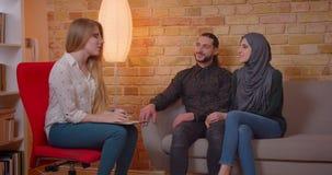 Zbliżenie krótkopęd uśmiecha się radośnie siedzieć na młoda szczęśliwa muzułmańska para dyskutuje z realter nowego mieszkanie zdjęcie wideo
