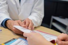 Zbliżenie lekarka i cierpliwa patrzeje broszura fotografia stock