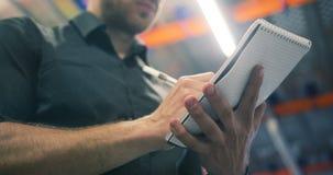 Zbliżenie logistyk business manager młodego człowieka magazynu pracownika doręczeniowy writing w jego notepad przy magazynową per zbiory wideo