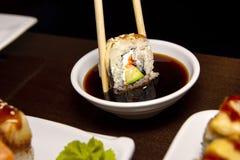 Zbliżenie mężczyzna je wyśmienicie suszi z chopsticks z jedzeniem w tle zdjęcie stock