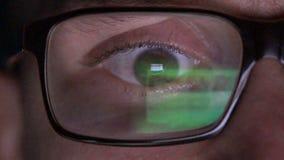 Zbliżenie mężczyzna oczy w szkłach pracują na laptopie przy nocą zdjęcie wideo