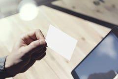 Zbliżenie mężczyzna Pokazuje Pustą Białą wizytówkę, Trzyma ręki Cyfrowego Nowożytną pastylkę Drewno stołu Zamazany tło Mockup Obraz Royalty Free