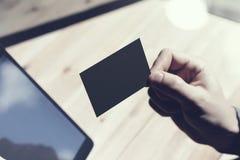 Zbliżenie mężczyzna Pokazuje Pustą Czarną wizytówkę, Trzyma ręki Cyfrowego Nowożytną pastylkę Drewno stołu Zamazany tło Mockup Zdjęcie Royalty Free