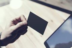 Zbliżenie mężczyzna Pokazuje Pustą Czarną wizytówkę, Trzyma ręki Cyfrowego Nowożytną pastylkę Drewno stołu Zamazany tło Mockup Zdjęcia Stock