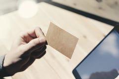 Zbliżenie mężczyzna Pokazuje Pustą rzemiosło wizytówkę, Trzyma ręki Cyfrowego Nowożytną pastylkę Drewno stołu Zamazany tło Mockup Zdjęcia Stock