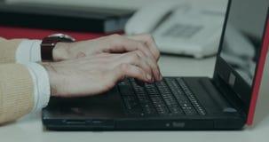 Zbliżenie mężczyzna wręcza klapanie na klawiaturze od notatnika zbiory wideo