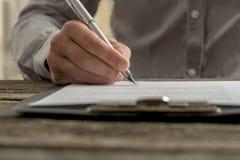 Zbliżenie męski ręki podpisywania biznesu kontrakt lub dokument Fotografia Stock