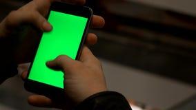 Zbliżenie męskie ręki trzyma mądrze telefon z zieleń ekranem prekeyed dla skutków zbiory
