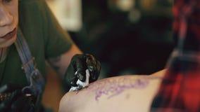 Zbliżenie młoda czerwona z włosami tatuażu artysty kobieta tatuuje obrazek na nodze klient nad nakreśleniem w studiu indoors zbiory