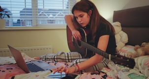 Zbliżenie młoda dama w piżamy na jej łóżkowym mieniu gitara i pisać na maszynie coś na jej notatce wtedy zaczyna śpiewać zbiory