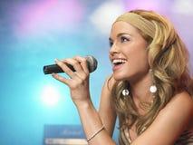 Zbliżenie młoda kobieta śpiew W mikrofon obraz royalty free