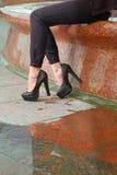 Zbliżenie młoda kobieta iść na piechotę na czerwonej granitowej brukowiec ulicie z kałużą i odbiciem Piękne kobiet nogi wewnątrz Zdjęcie Royalty Free
