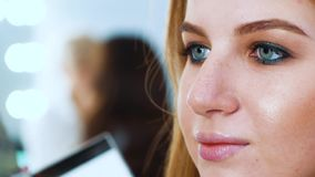 Zbliżenie młoda kobieta z niebieskimi oczami i czerwona włosiana kładzenie wargi glosa z makeup szczotkujemy zbiory wideo