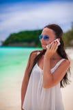 Zbliżenie młoda piękna kobieta opowiada dalej przy plażą Obrazy Stock