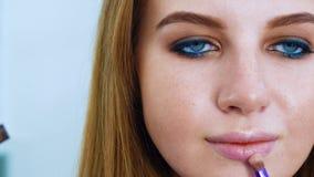 Zbliżenie młoda piękna kobieta z niebieskimi oczami i czerwona włosiana kładzenie wargi glosa z makeup szczotkujemy zbiory