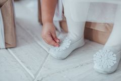 Zbliżenie młode balerin nogi, siedzi w pointe butach z płatka śniegu wystrojem przy białym drewnianym podłogowym tłem balet Zdjęcia Royalty Free