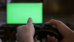 Zbliżenie młode męskie ręki bawić się na wideo gry konsoli kontroluje joystick na chroma klucza zieleni ekranu TV ekranie - zbiory
