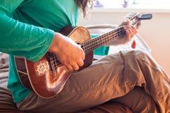 Zbliżenie młodego człowieka ` s wręcza bawić się gitara akustyczna ukulele przy domem Mężczyzna mienia ukulele Obraz Stock