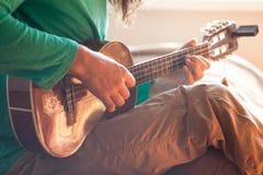 Zbliżenie młodego człowieka ` s wręcza bawić się gitara akustyczna ukulele przy domem Mężczyzna mienia ukulele Zdjęcia Stock