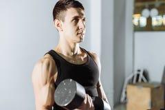Zbliżenie młodego człowieka udźwigu mięśniowi ciężary w gym Obrazy Royalty Free
