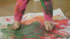 Zbliżenie młodego dziecka ` s nożny guasz plamiący w farbie Dziecko chodzi na wielkim prześcieradle biały papier zdjęcie wideo