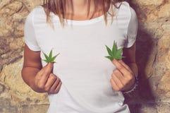 Zbliżenie młodej kobiety mienia marihuana opuszcza w ona ręki obraz royalty free
