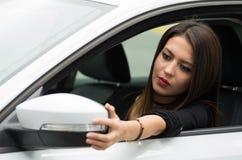 Zbliżenie młodej kobiety obsiadanie w samochodowym przystosowywa strony lustrze, jak widzieć od outside kierowcy okno, żeński kie Zdjęcie Stock