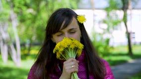 Zbliżenie młodej kobiety obwąchania koloru żółtego Dandelions zbiory