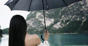 Zbliżenie młodej kobiety pobyt z ona z powrotem i nagi ramię kamera pod jej czarnym parasolem i jesteśmy przyglądający zadziwiać zbiory