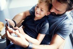 Zbliżenie młody chłopiec obsiadanie z ojcem i używać smartphone w nowożytnym pogodnym miejscu Horyzontalny, zamazany tło, Obraz Royalty Free