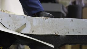 Zbliżenie młody człowiek w meblarskiej fabryce która ciie nadmierne piankowe części kanapa zbiory