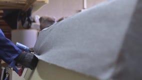 Zbliżenie młody człowiek w meblarskiej fabryce która stawia wpólnie jeden część kanapa z zszywaczem zbiory