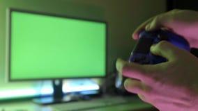 Zbliżenie młody człowiek wręcza bawić się wideo gry na hazard konsoli przed TV widescreen zbiory wideo